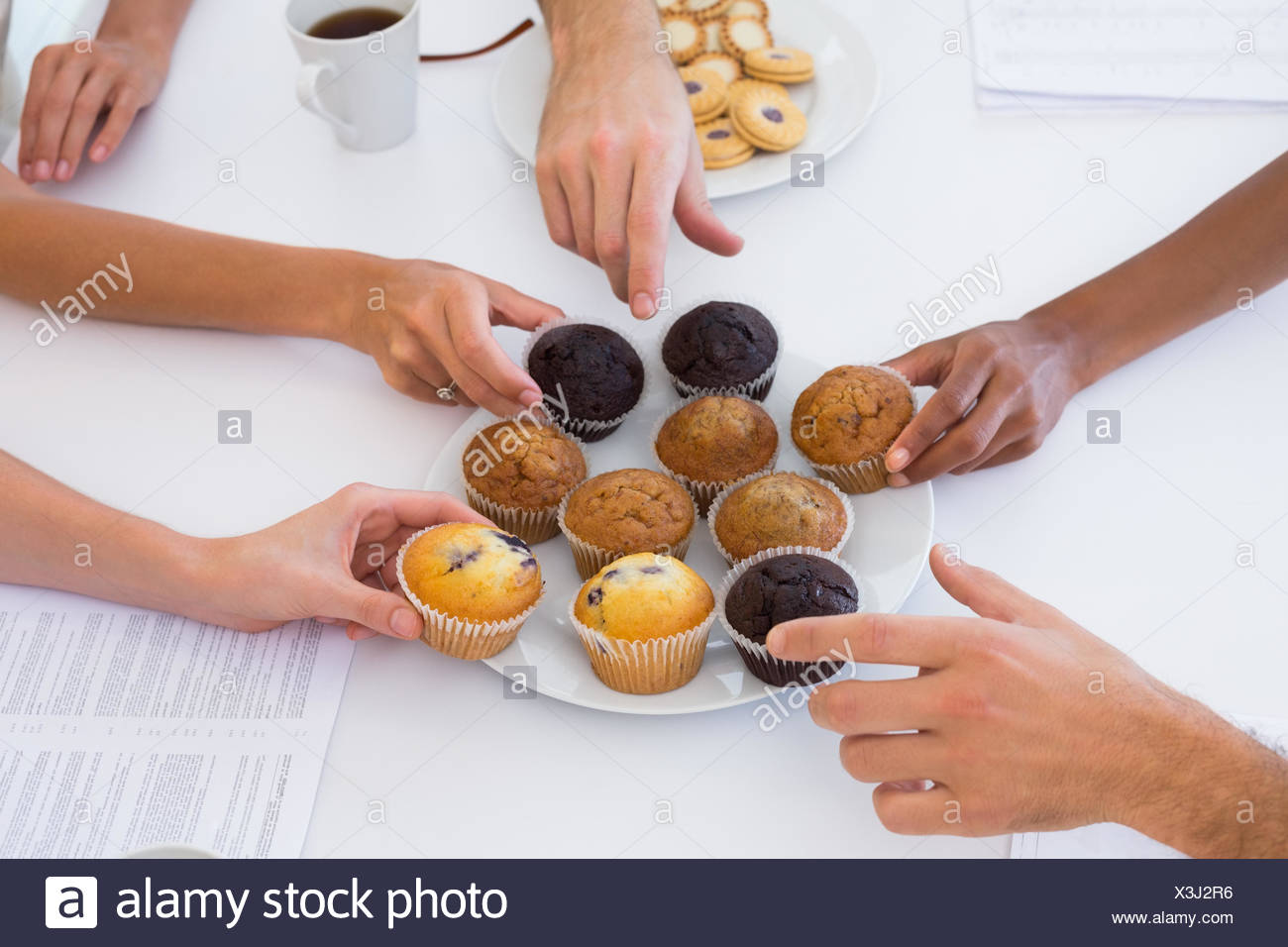 Hungry workers grabbing muffins - Stock Image