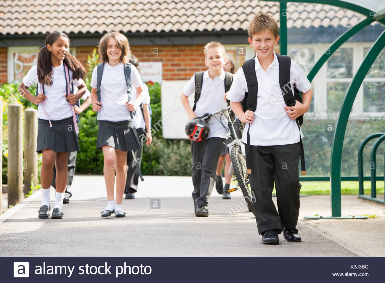 Students leaving school one with a bicycle Stock Photo