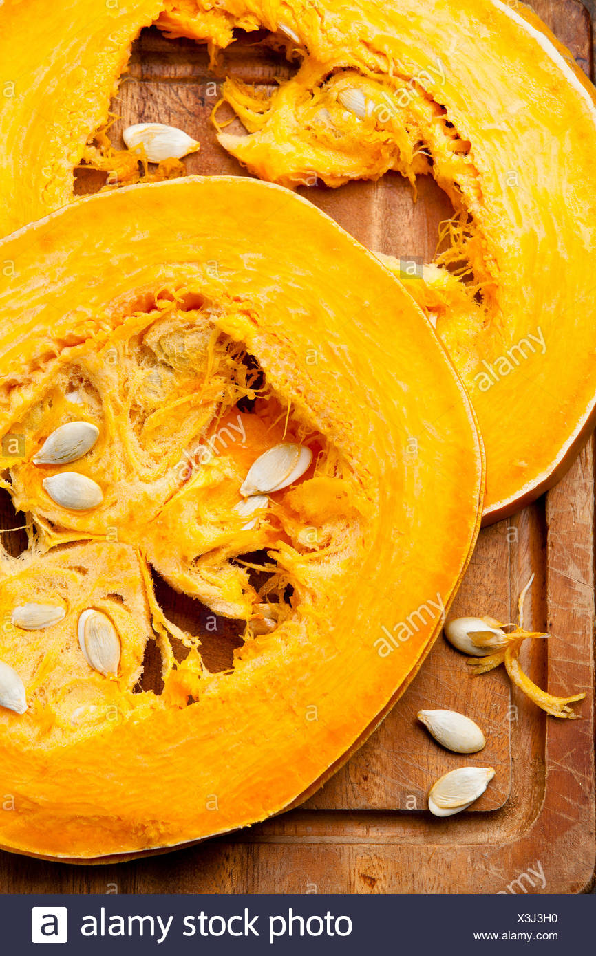 Cut a piece of ripe pumpkin on wooden background - Stock Image