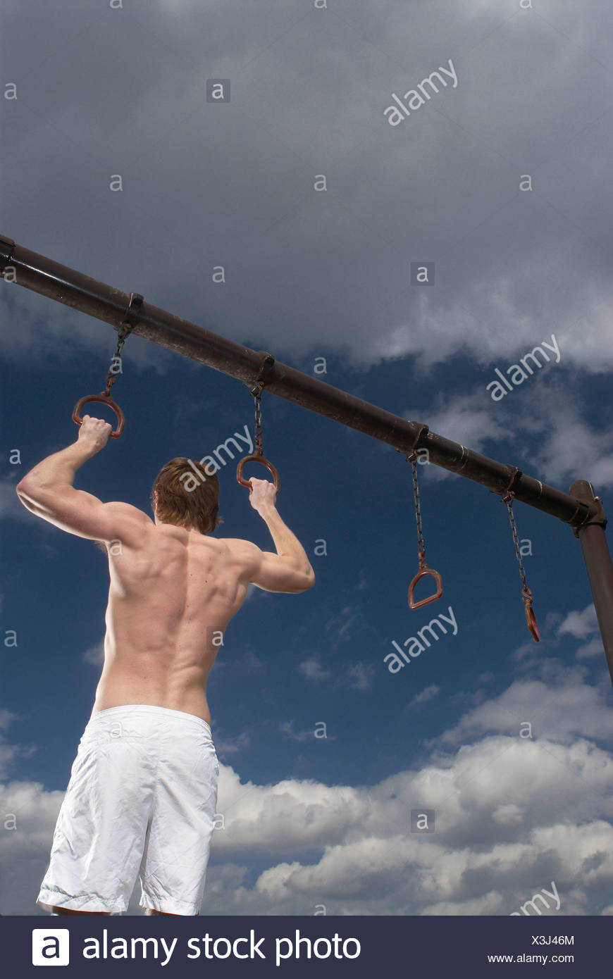 man holding pull up rings - Stock Image