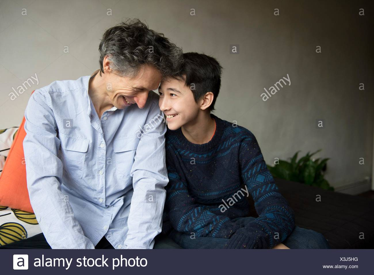 Teenage boy and father face to face on sofa - Stock Image