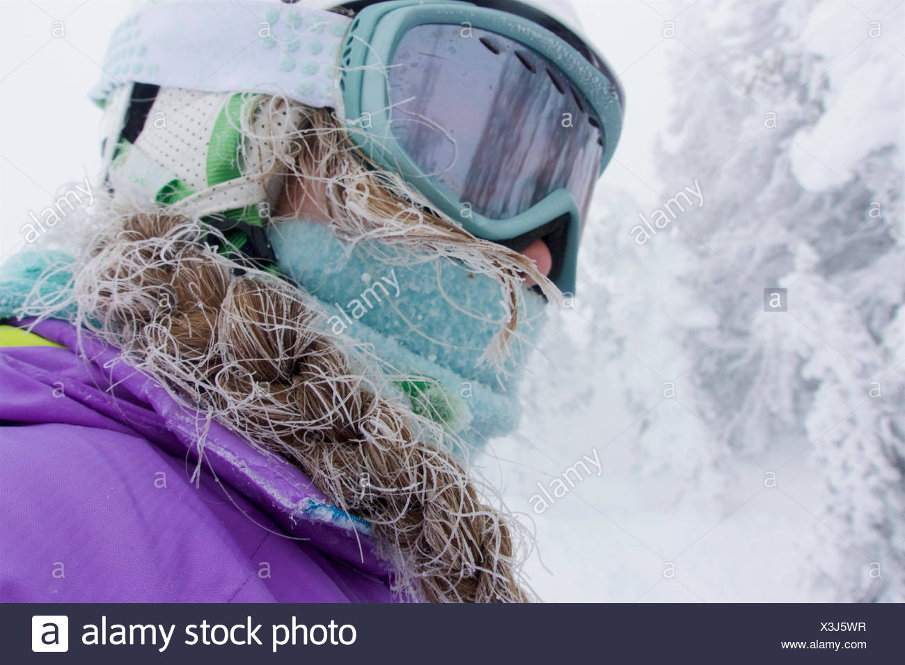 A teenage girl, with frosted hair from skiing in a cold fog, in the Grand Targhee mountains. - Stock Image
