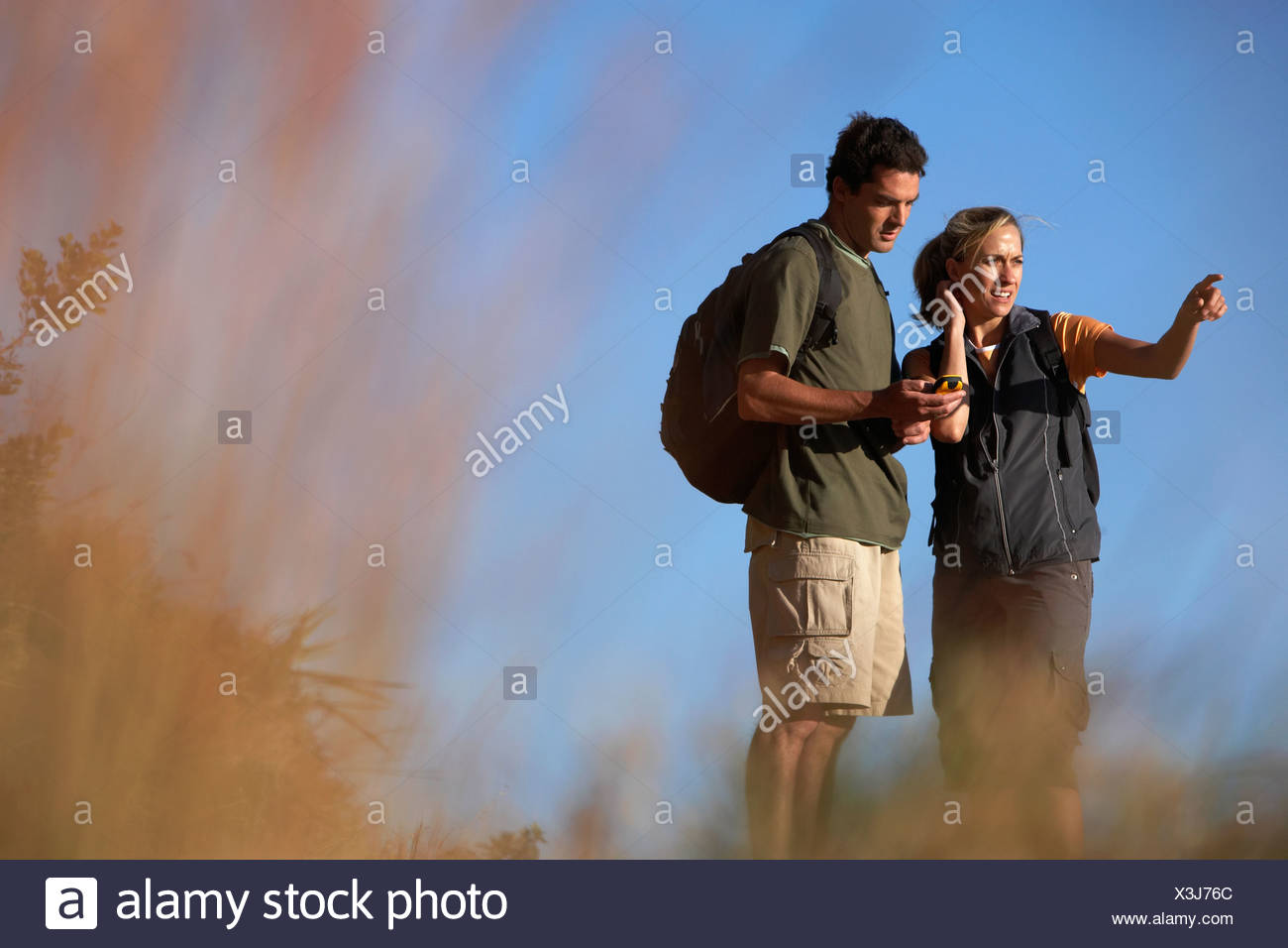 Couple hiking man holding navigation system woman pointing focus on background - Stock Image