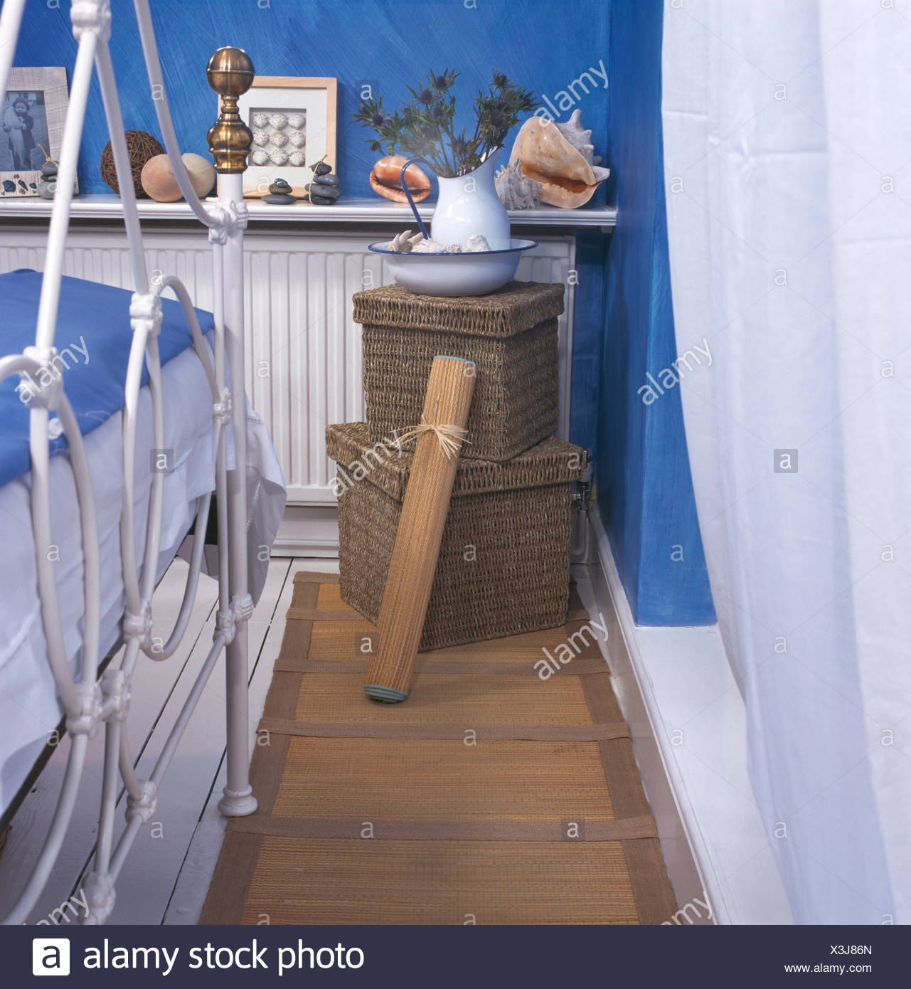 Seagrass storage boxes in bright blue economy style bedroom ...
