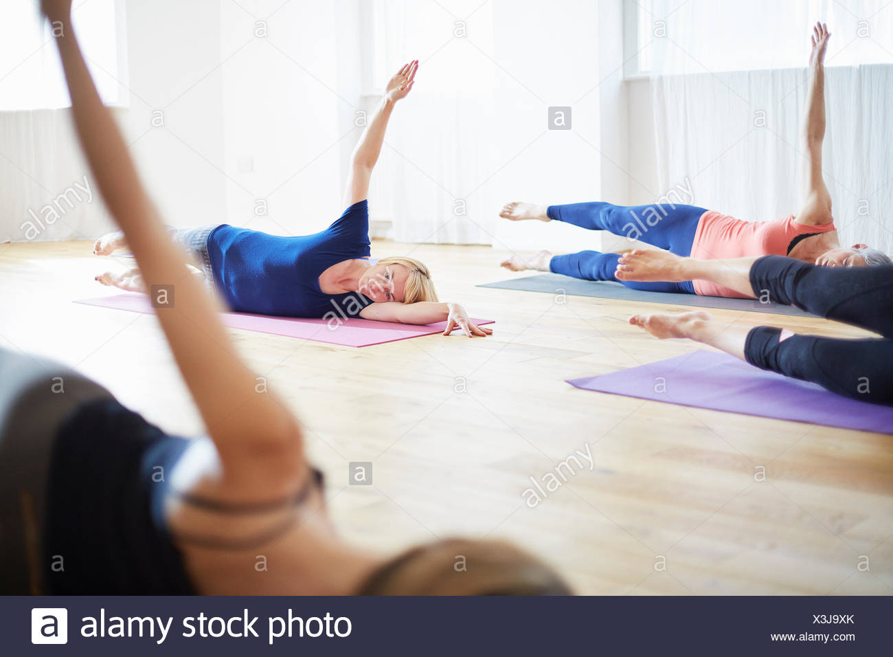 Four women lying on side with arms raised in pilates class - Stock Image