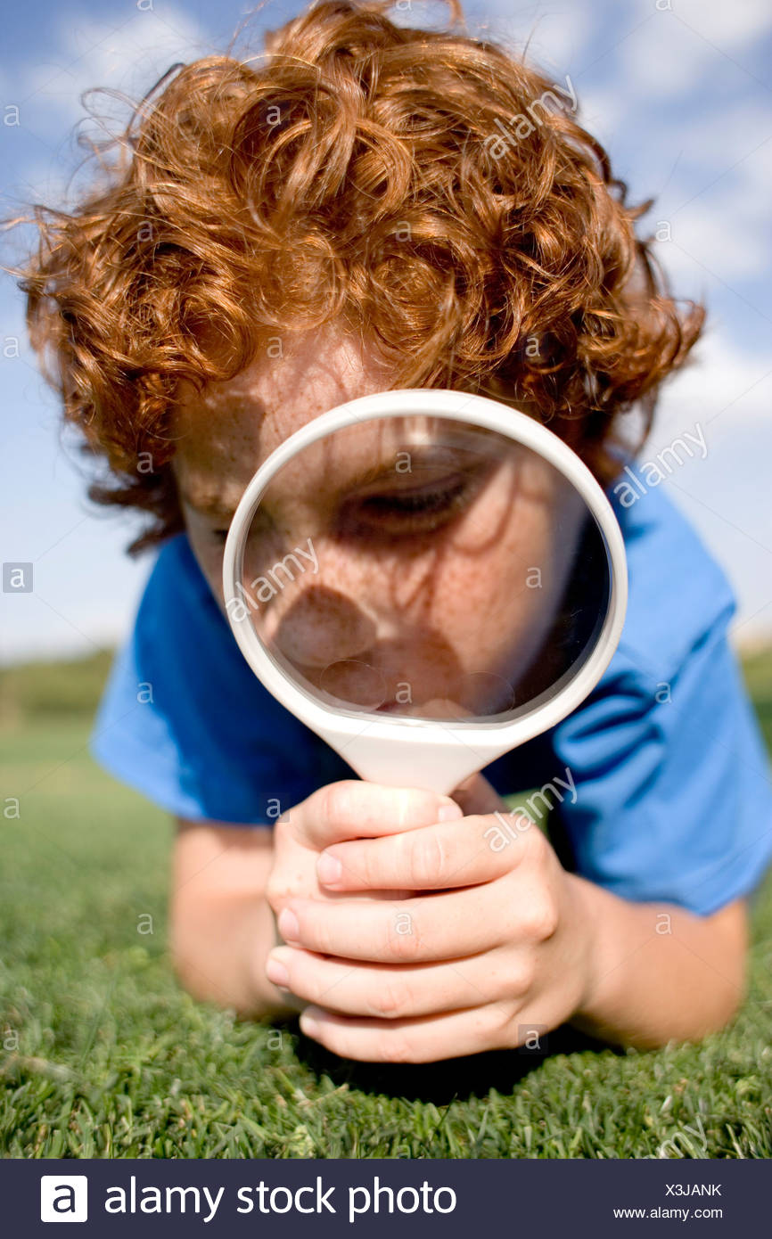 Boy using a magnifying glass to examine an area of grass. Stock Photo