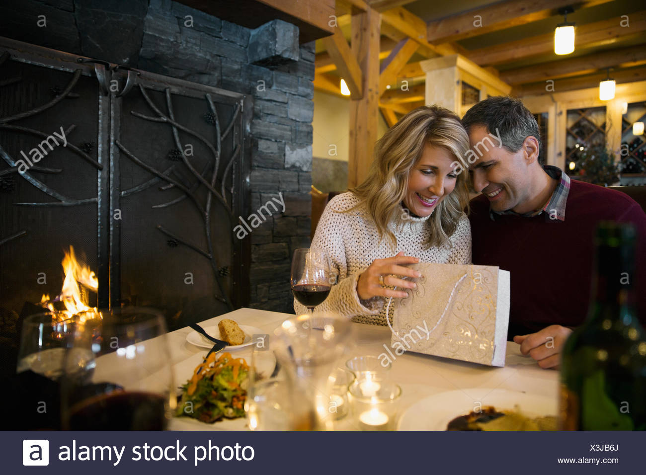 Man giving woman gift at fireside restaurant table - Stock Image