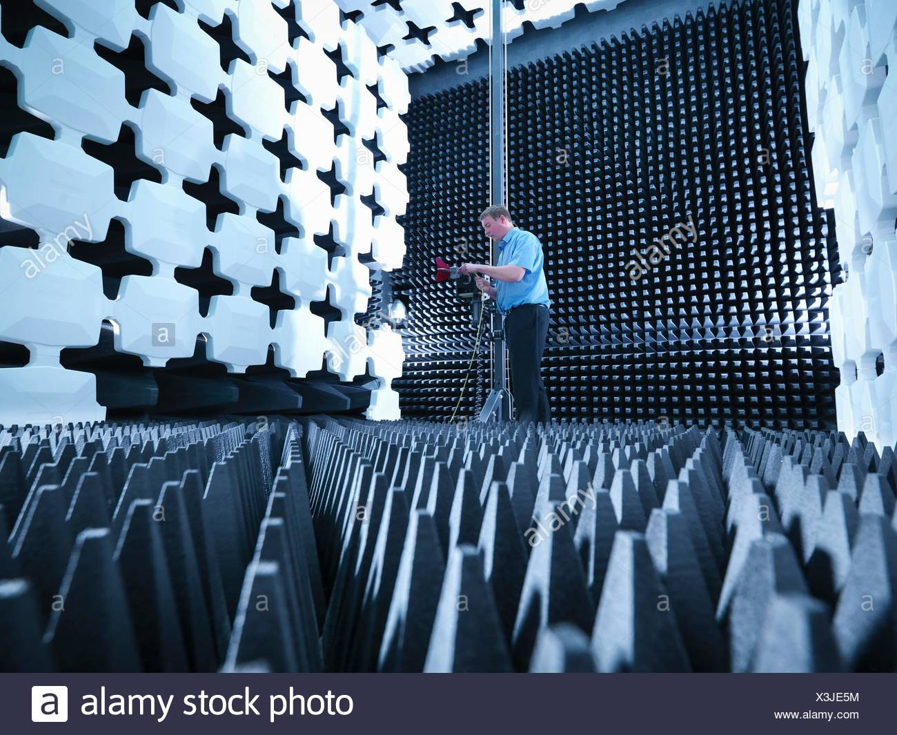 Engineer in anechoic chamber with horn antenna set up for Electromagnetic compatibility (EMC) radiated emission testing - Stock Image