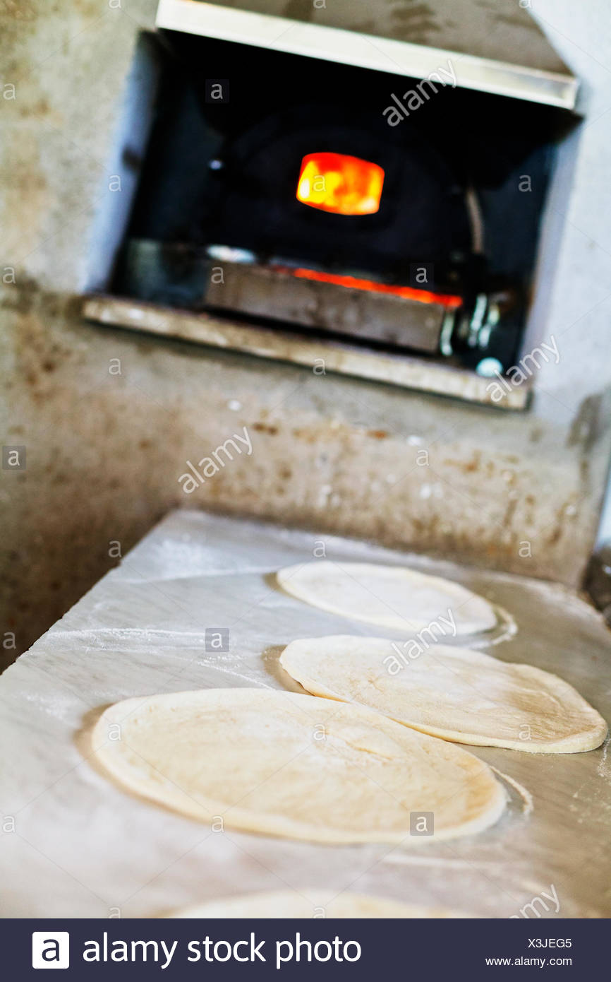 Pizza bases on counter against oven at restaurant kitchen - Stock Image
