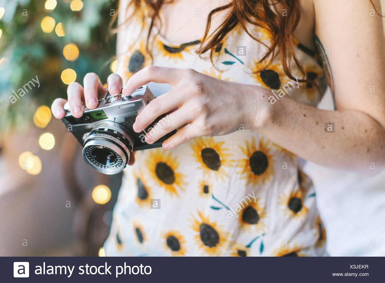 Young woman SLR camera, mid section - Stock Image