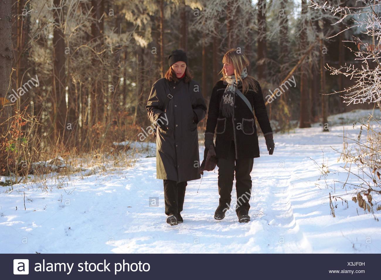Two women walk in a winter landscape - Stock Image