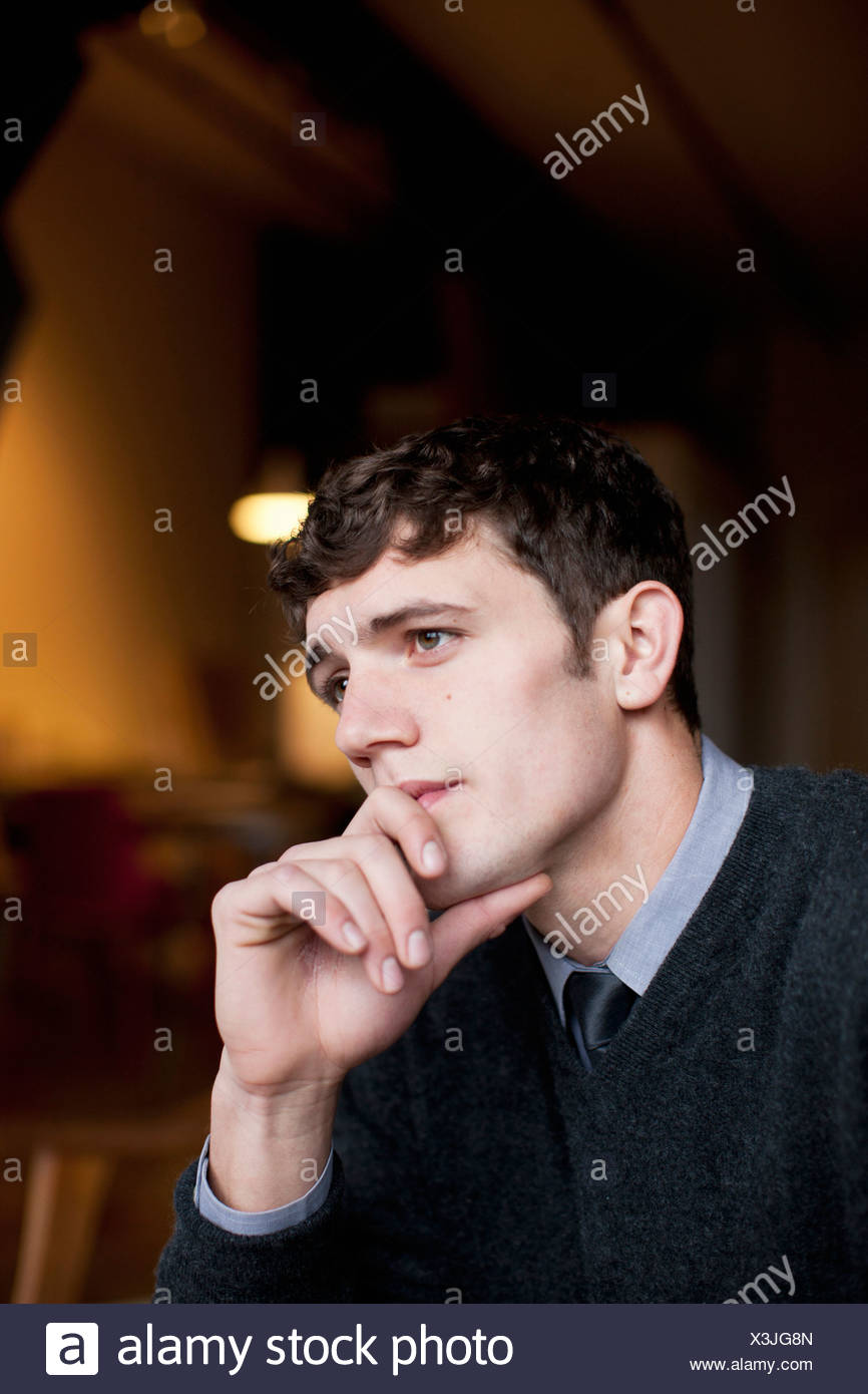 Businessman thinking with chin in hand - Stock Image
