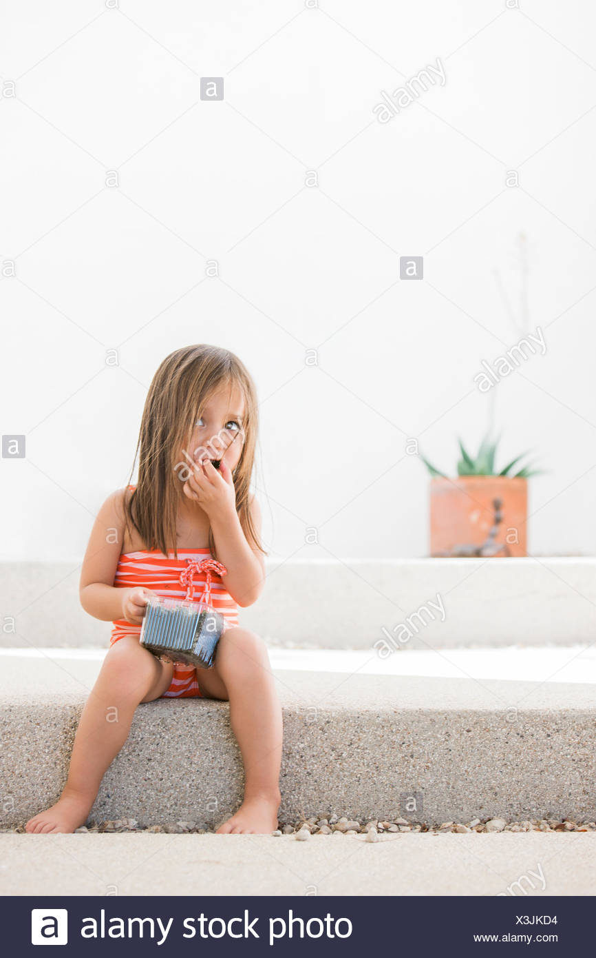 Toddler girl in bathing suit eating blueberries on patio - Stock Image