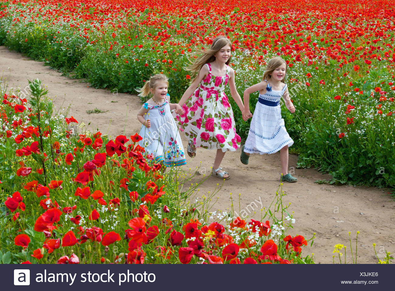 Girls running on dirt path - Stock Image