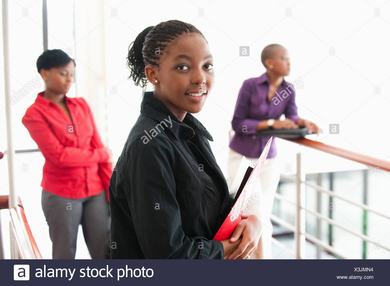 Portrait of young businesswoman with two women in background, Johannesburg, Gauteng Province, South Africa - Stock Image