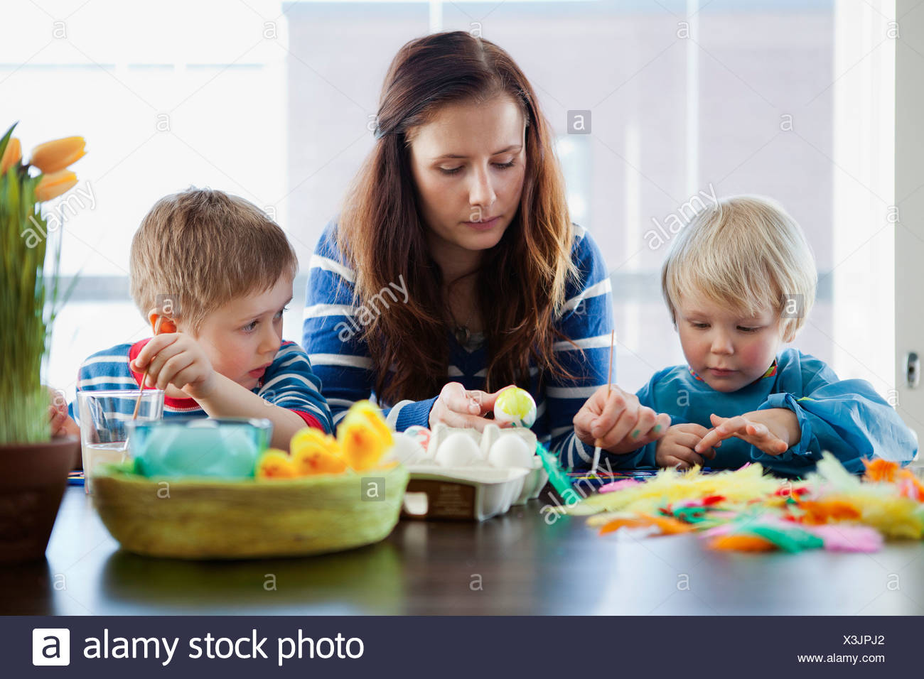 Mother with two children (2-3), (4-5) making Easter eggs - Stock Image
