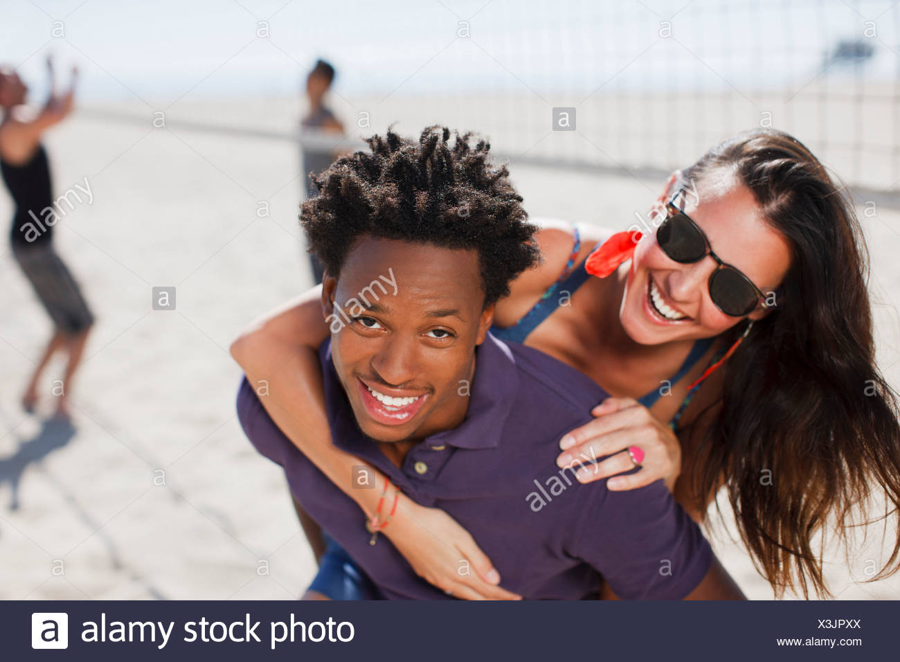 Couple playing together on beach - Stock Image