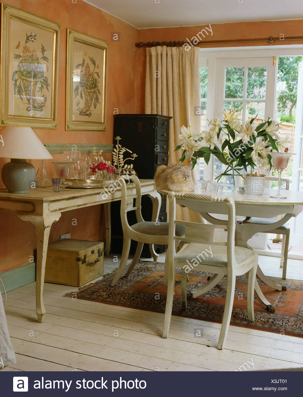 White painted table and chairs in peach cottage dining room ...