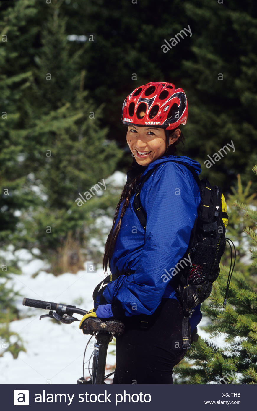 Female mountain biker taking a break from riding snowy, springtime trails, British Columbia, Canada. - Stock Image