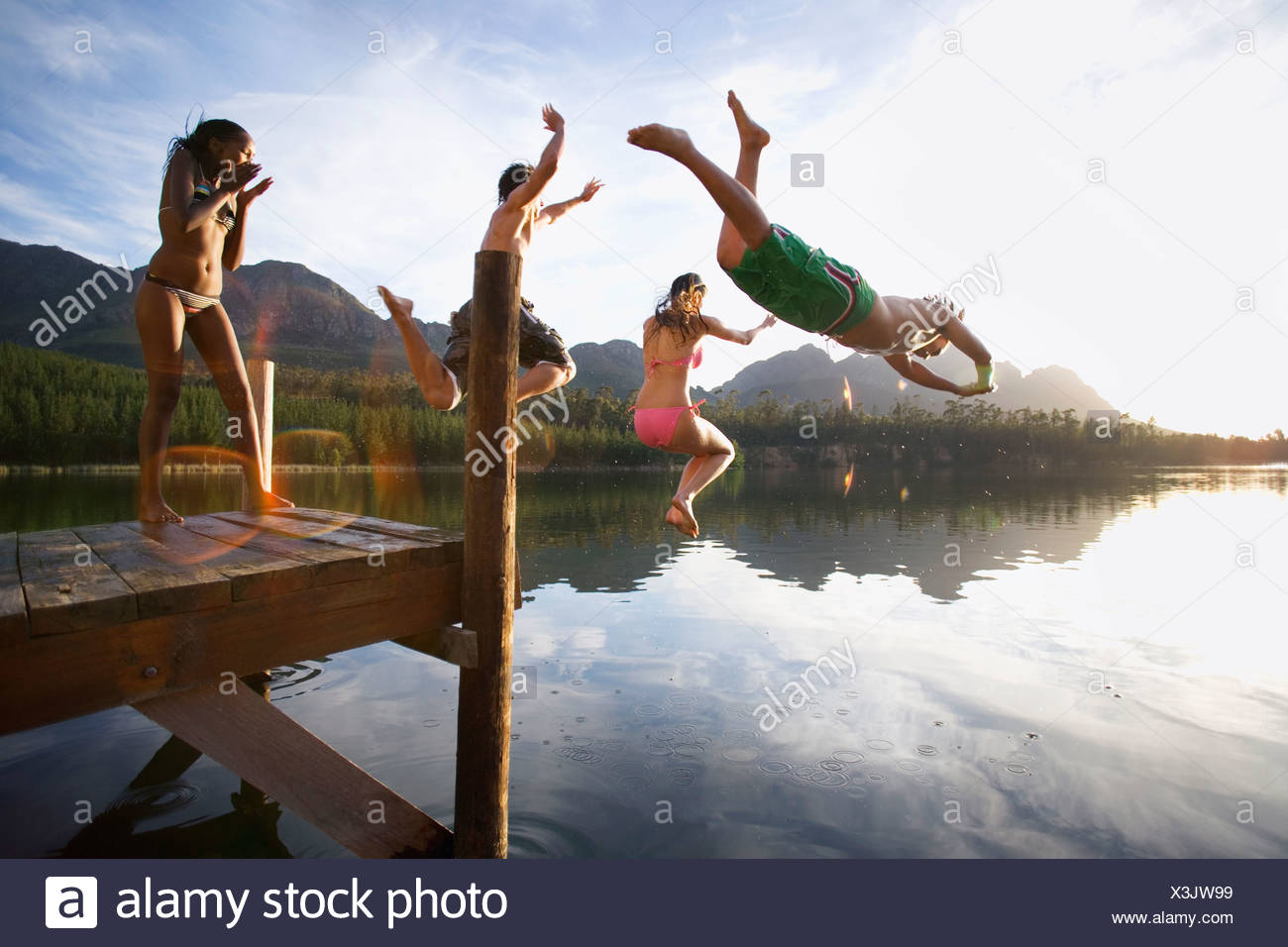 Four young adults diving from jetty into lake at sunset side view lens flare - Stock Image