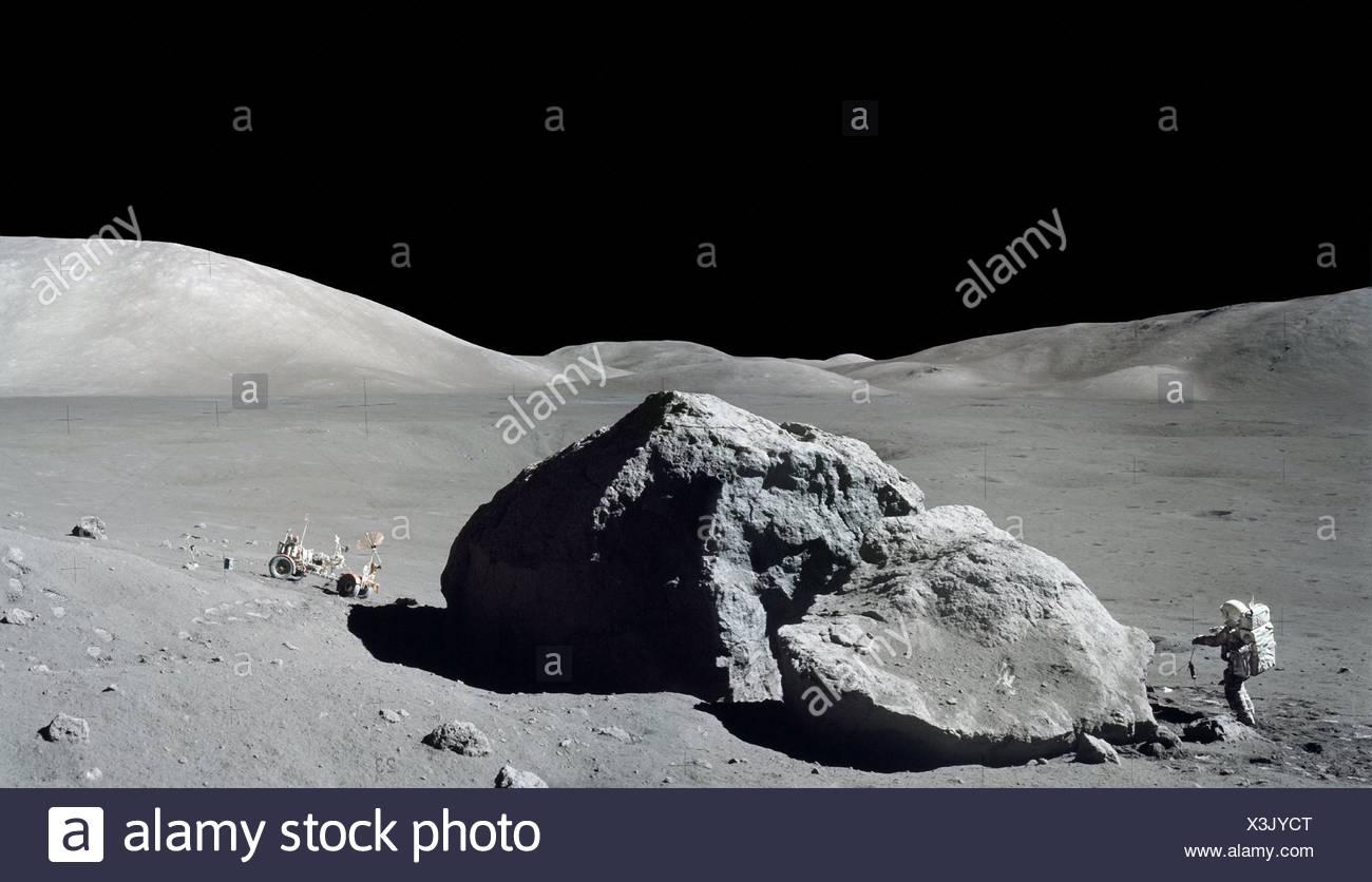 Apollo 17 astronaut Harrison Schmitt examines a huge boulder during the final moonwalk of the last lunar landing of the Apollo program. - Stock Image