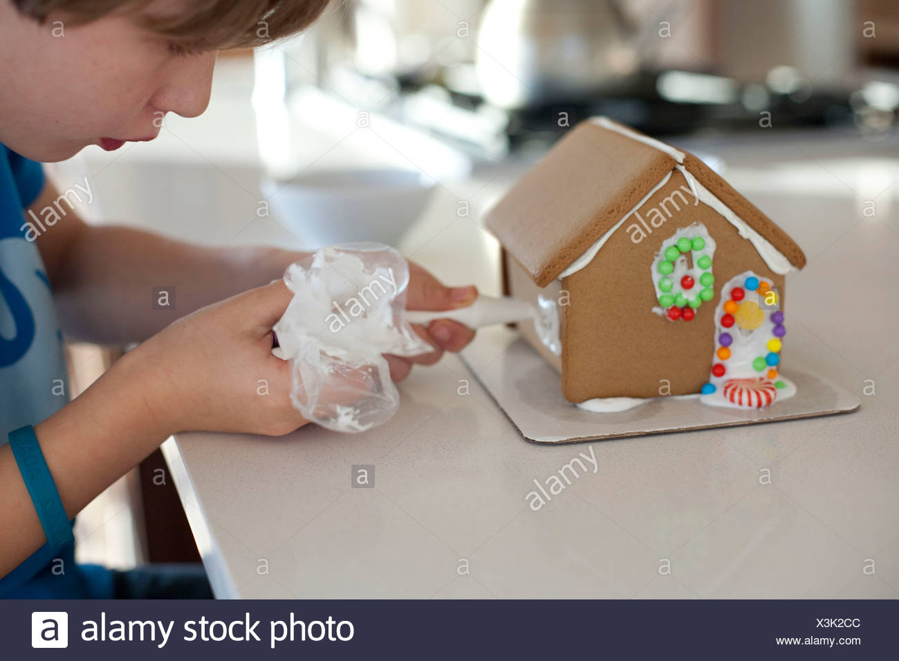 Boy decorating gingerbread house - Stock Image