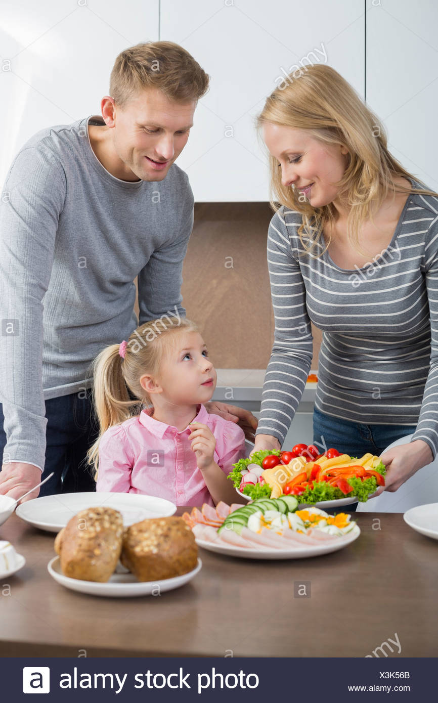 Happy parents with daughter having meal in kitchen - Stock Image