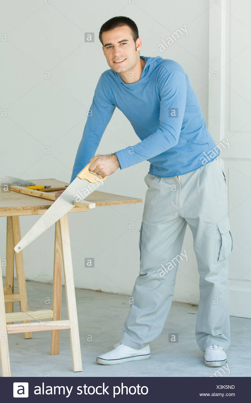 Improvement do it yourself handyman project projects stock photos man sawing piece of wood looking at camera stock image solutioingenieria Gallery