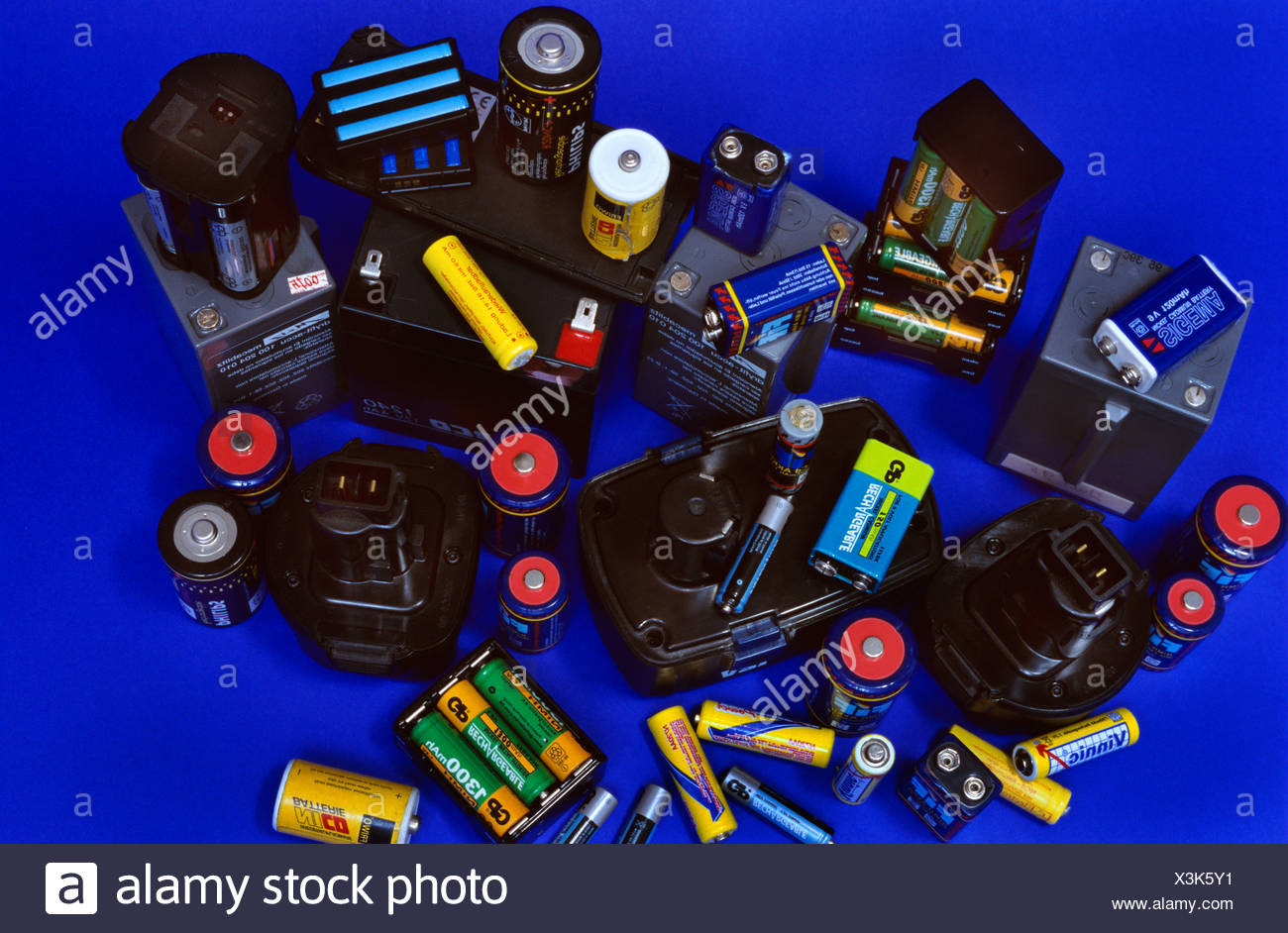Old rechargeable batteries against a blue backdrop Stock Photo