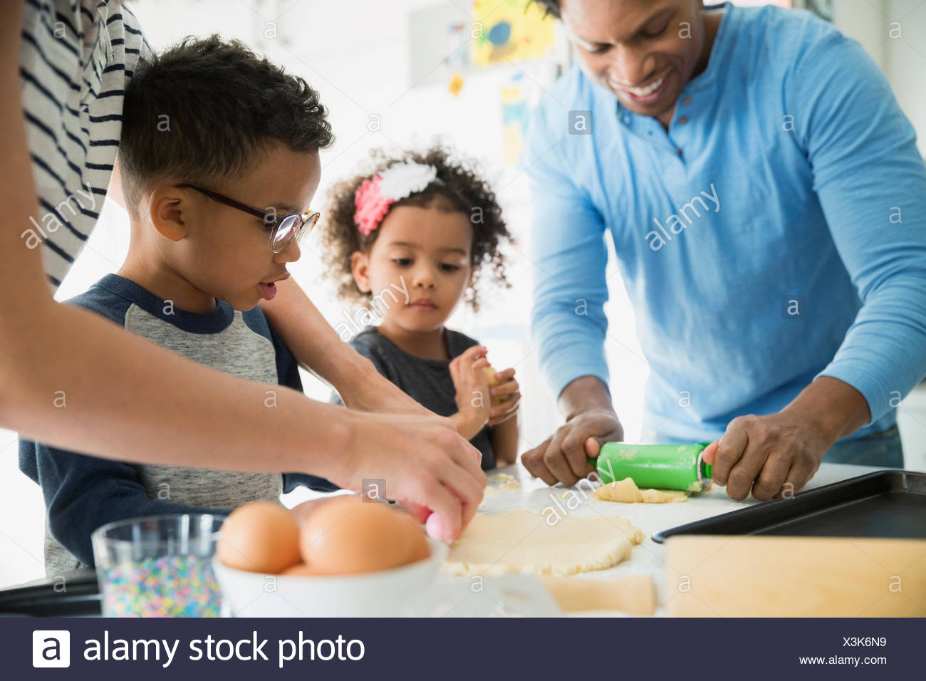 Family baking rolling out cookie dough - Stock Image