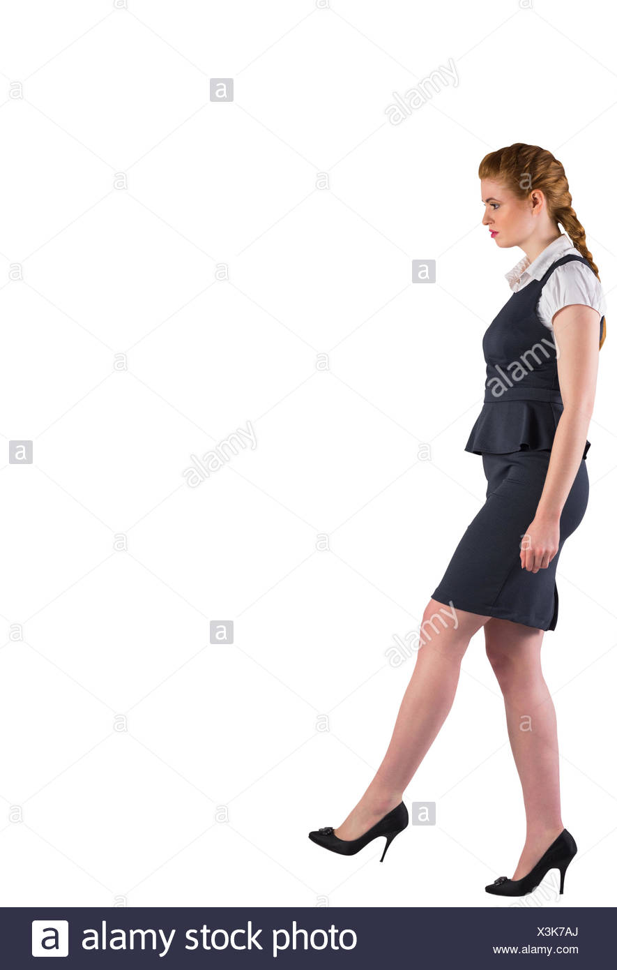 Redhead businesswoman stepping ahead - Stock Image