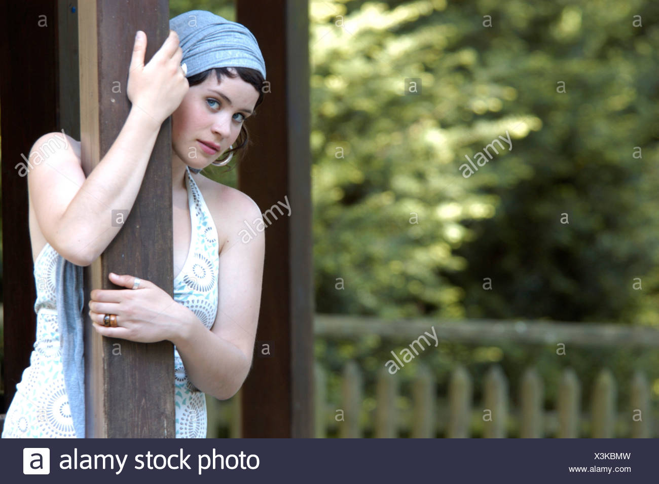 portrait of a beautiful woman with headress, leaning on a post, Germany Stock Photo
