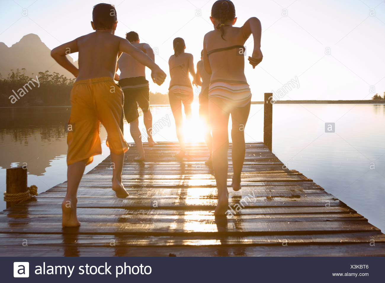 Family in swimwear running along jetty jumping into lake at sunset rear view lens flare - Stock Image