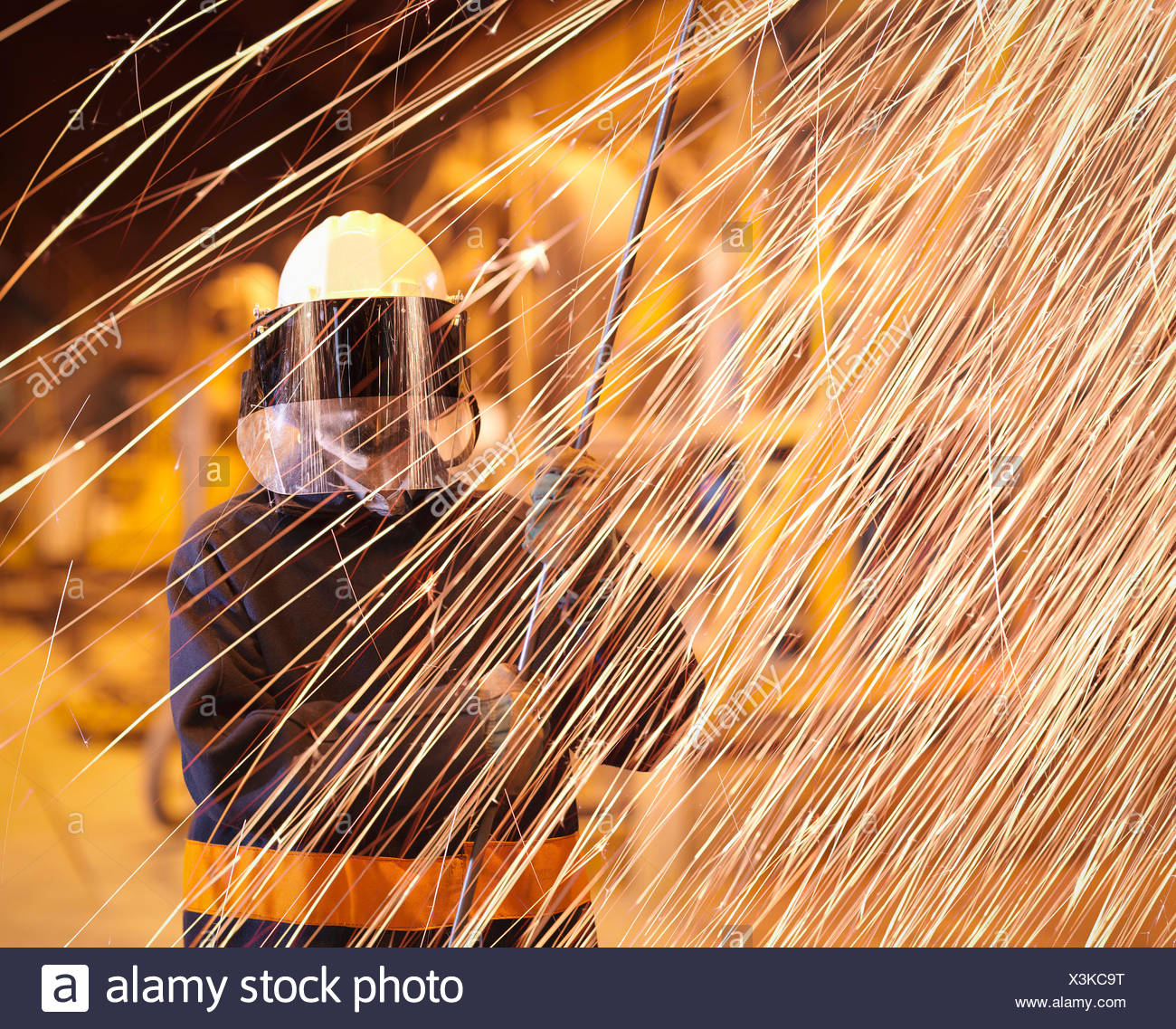 Steelworker holding sample lance behind sparks in steelworks - Stock Image