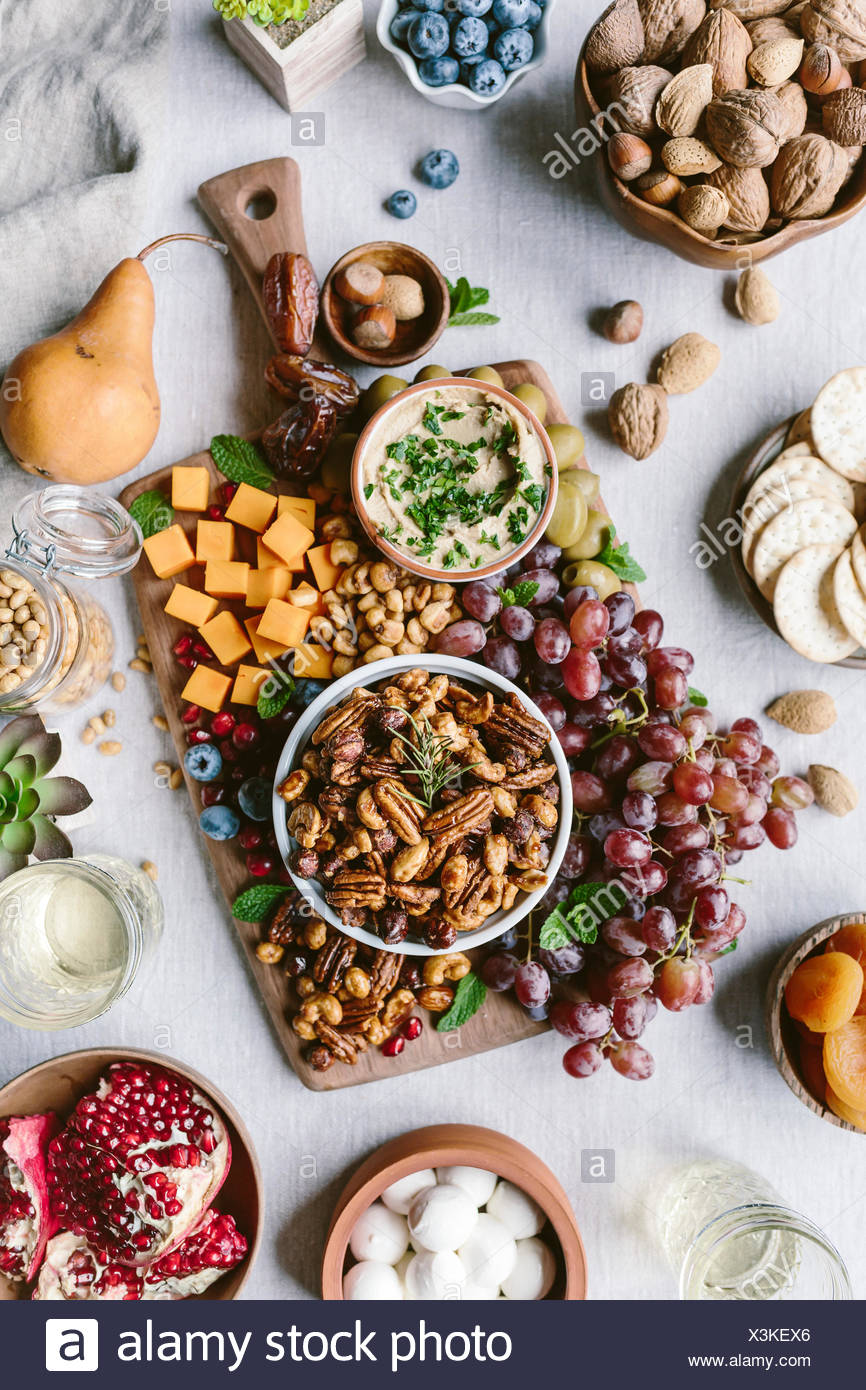 A bowl of spicy candied pecans are photographed as a part of a cheese and fruit board. - Stock Image