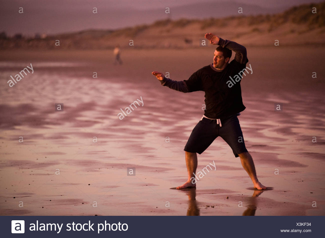 One mid adult man practices Taekwondo on the beach at sunset in Morro Bay, California. - Stock Image