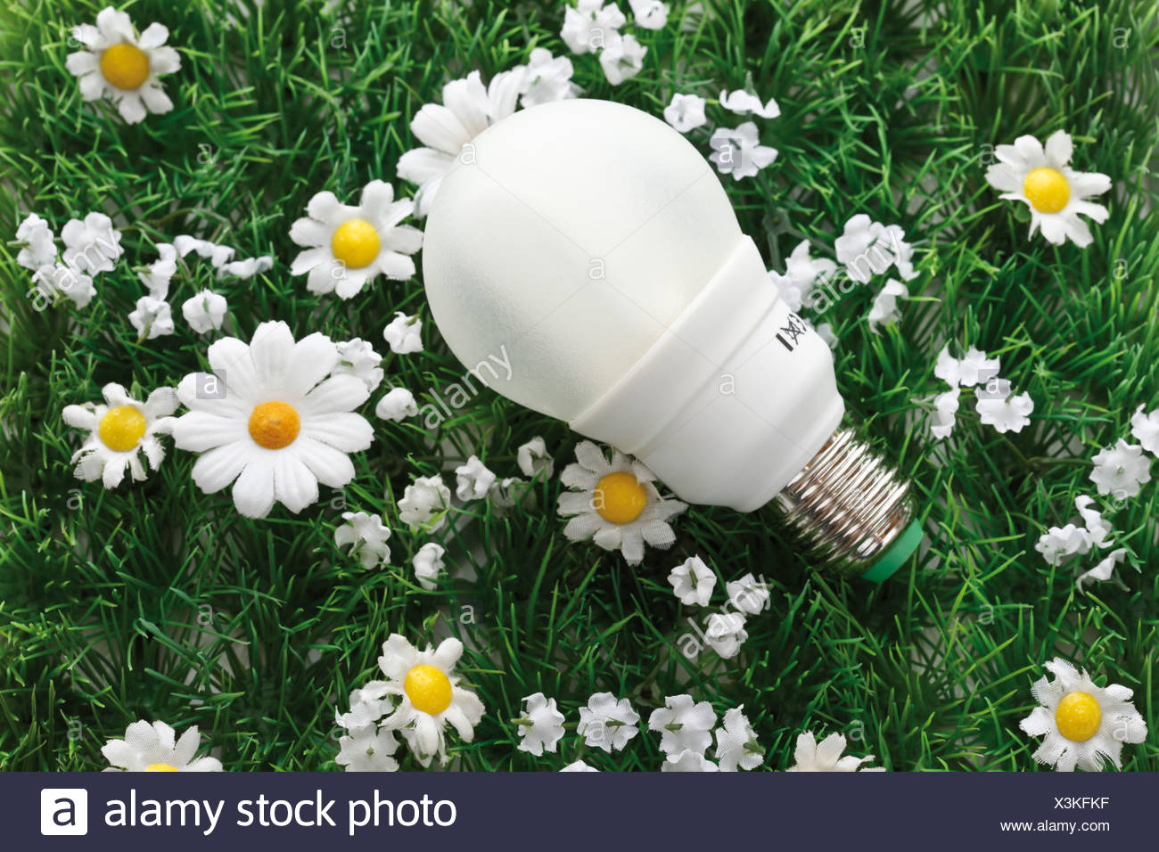 Energy saving lightbulb on synthetic turf, elevated view - Stock Image