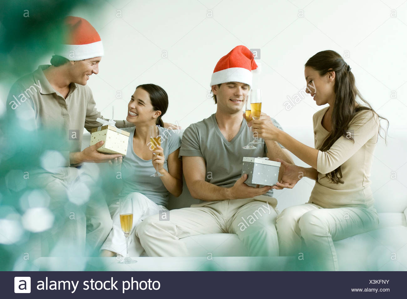 Two couples exchanging Christmas gifts, drinking champagne, men wearing Santa hats - Stock Image