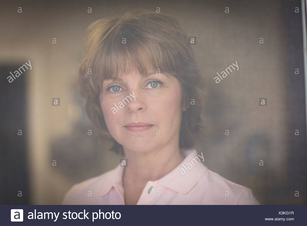 Portrait of mid adult woman, pensive expression - Stock Image