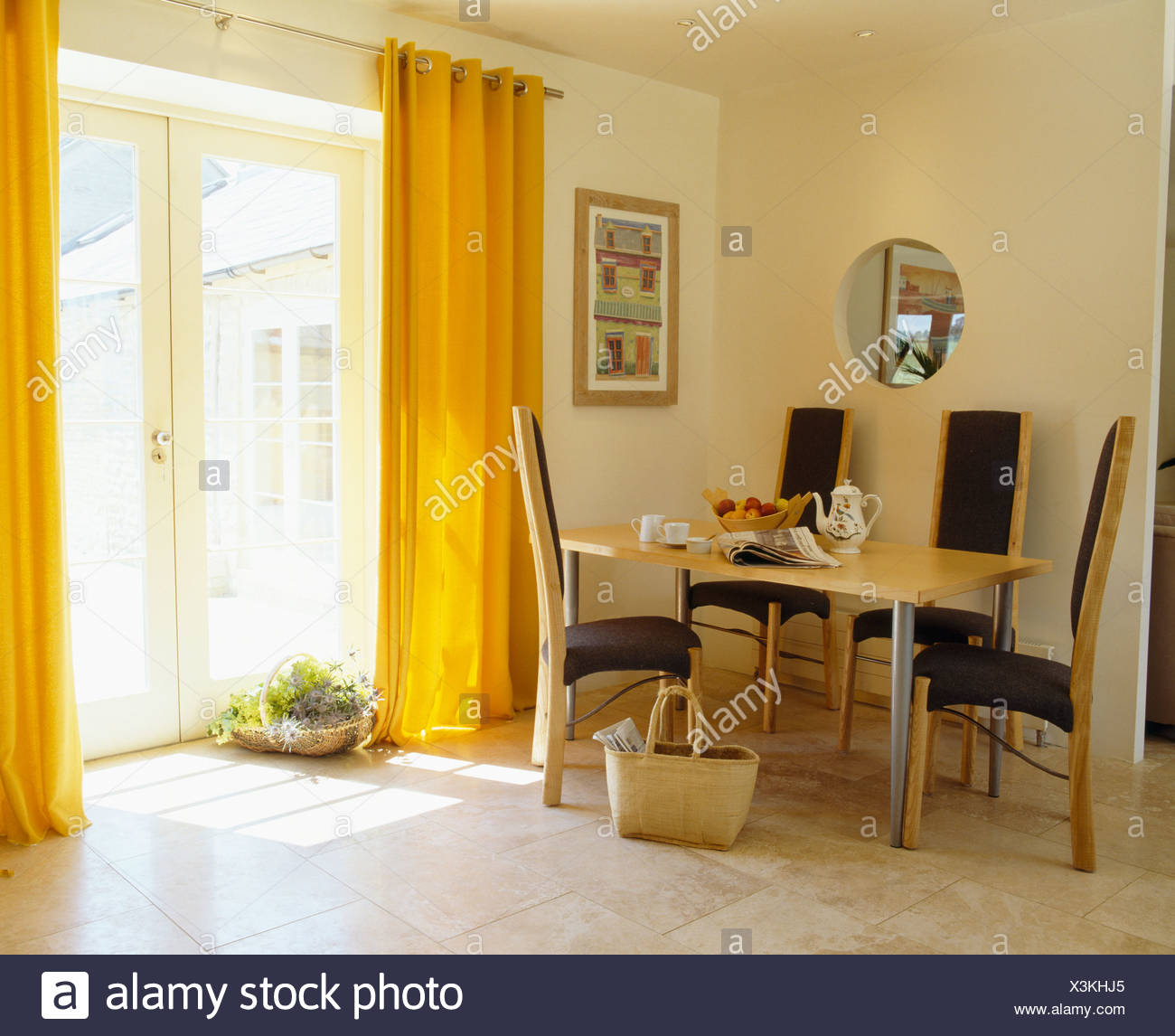 Yellow Curtains And Limestone Flooring In Modern Dining Room With Tall Back Chairs At Simple Table Stock Photo Alamy