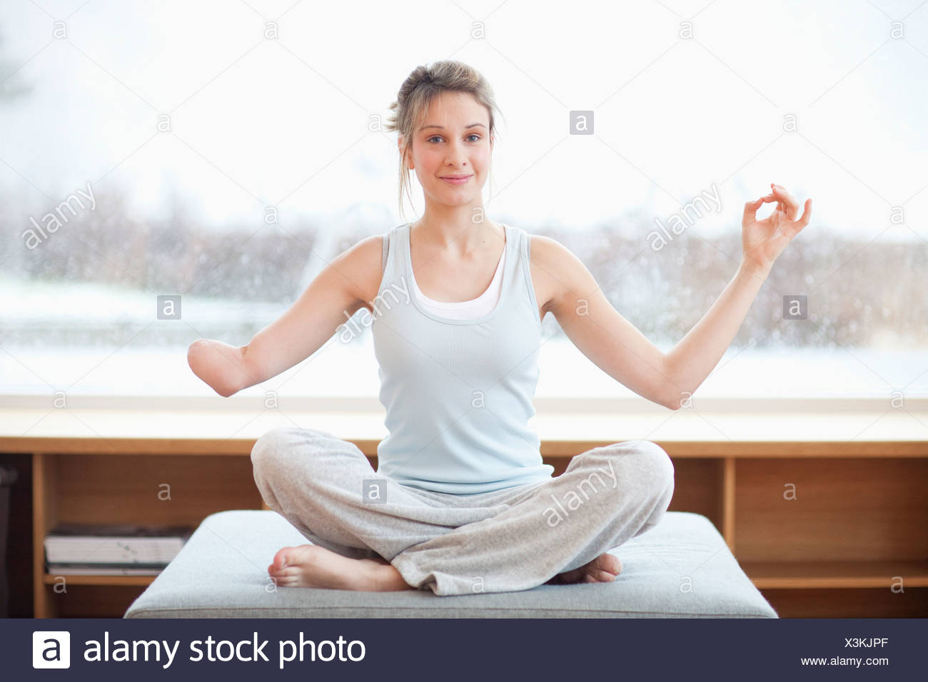 Young woman with amputee arm in yoga pose - Stock Image
