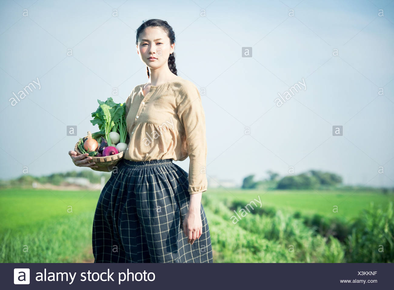 Young woman in field holding basket of homegrown vegetables - Stock Image