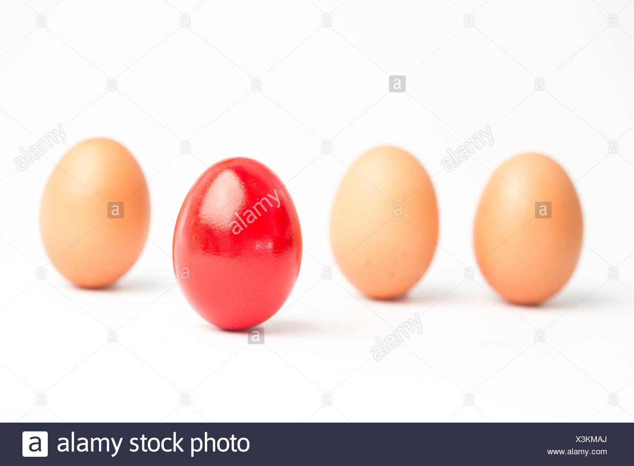 Four eggs in a row with one red one standing out on white background - Stock Image
