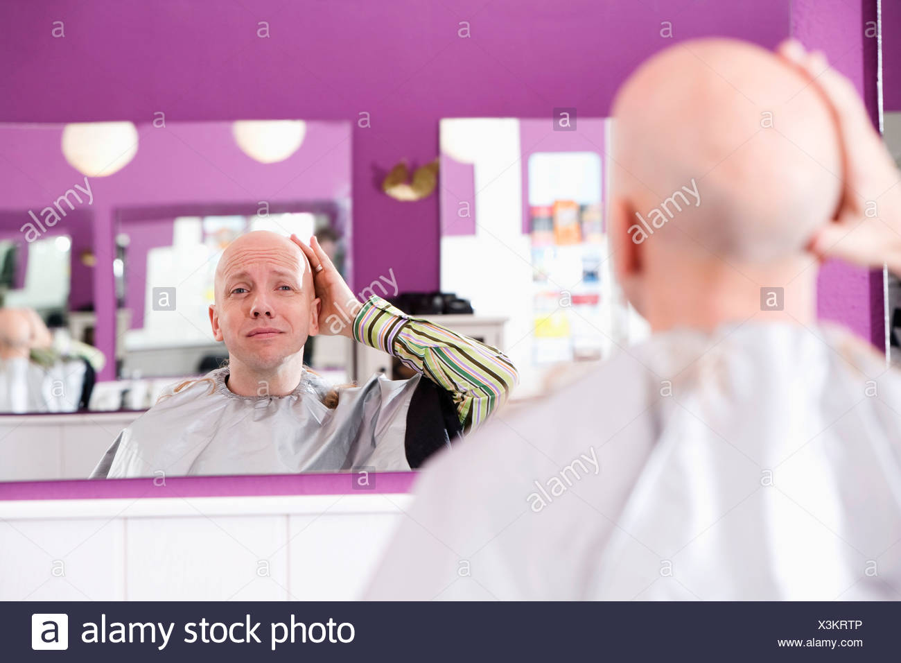 bald man at hair dresser looking into mirror - Stock Image