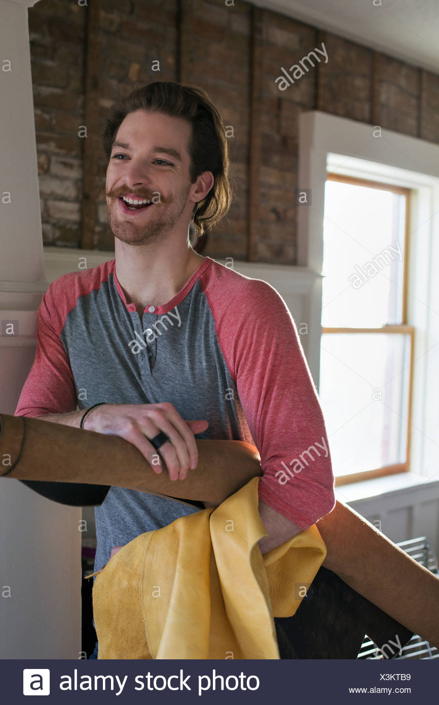 Happy man holding rolled up leather in workshop - Stock Image
