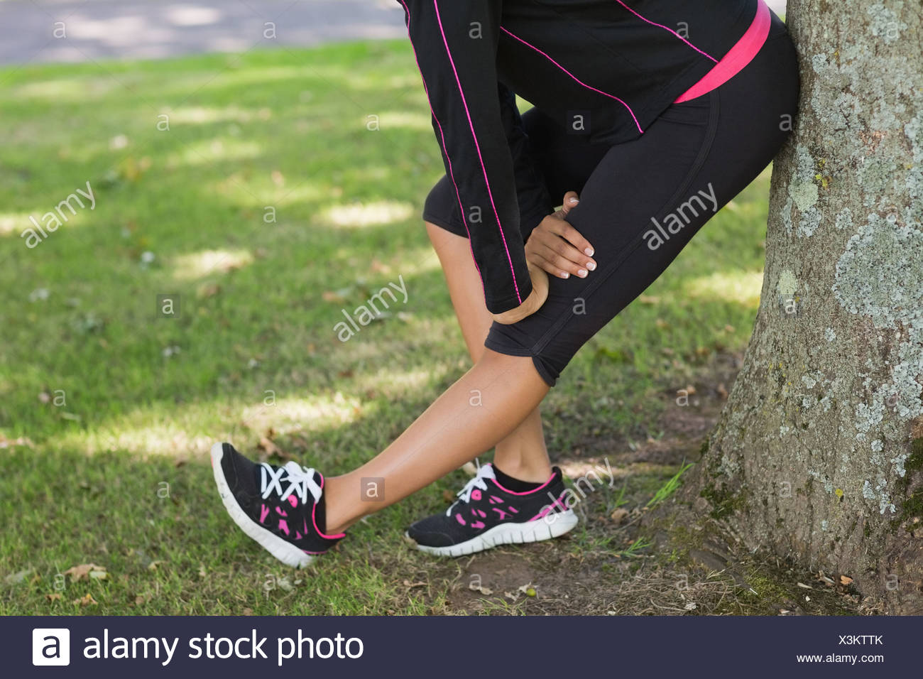 Low section of woman stretching her leg during exercise at park Stock Photo