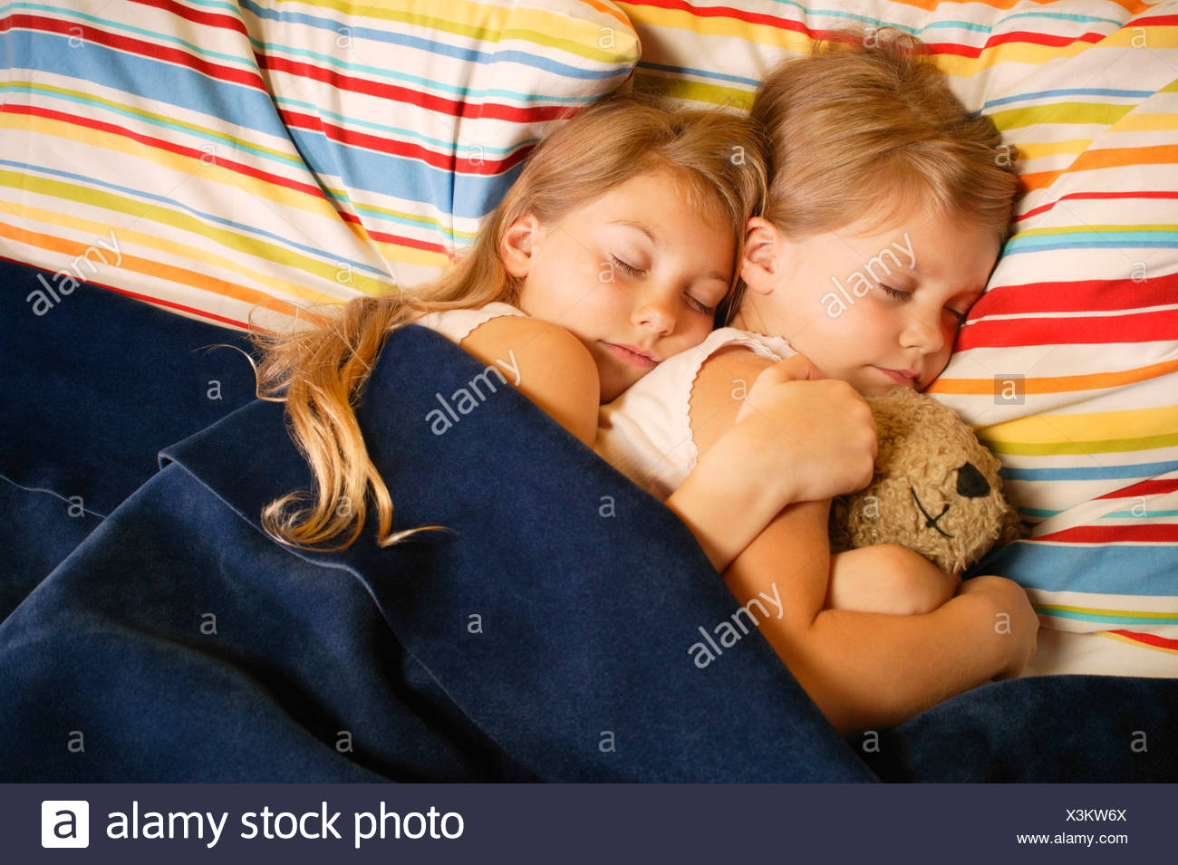 Sisters snuggle while taking a nap. - Stock Image