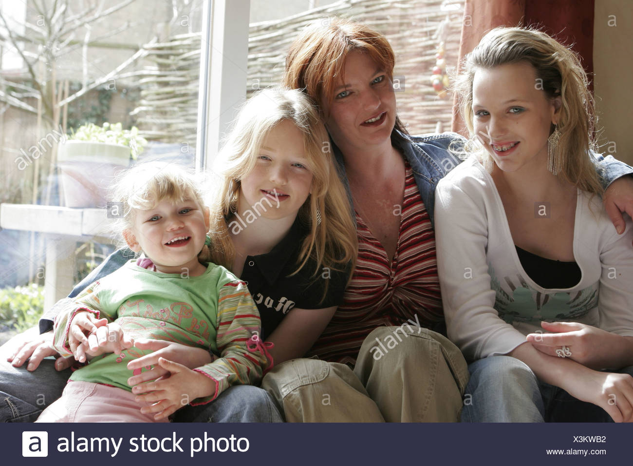 Mid aged woman posing with her three children at home on couch - Stock Image
