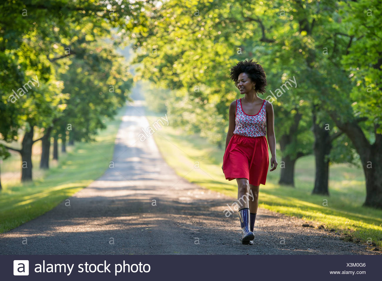 A woman walking down a tree lined path. - Stock Image