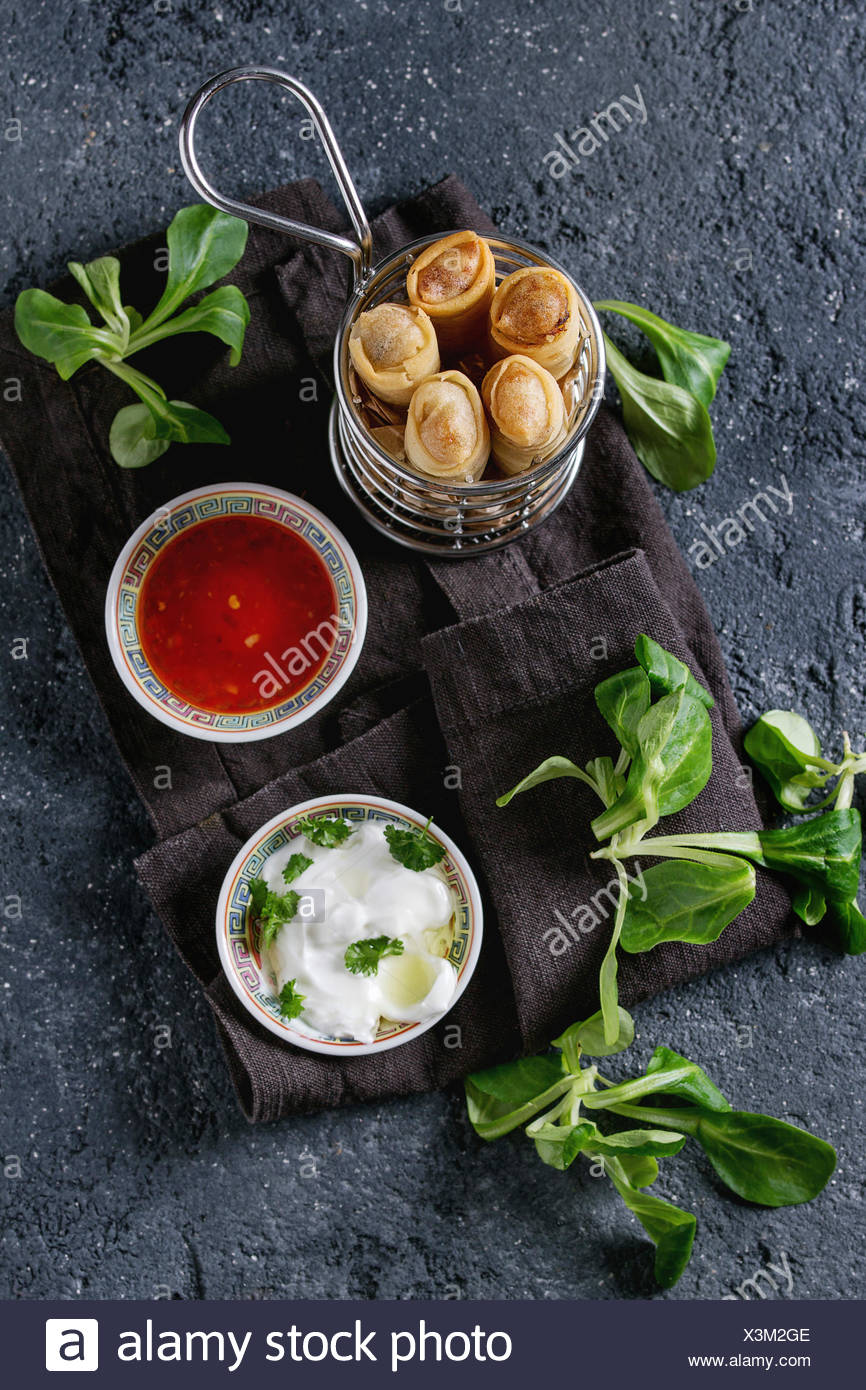 Fried spring rolls with red and white sauces, served in traditional china plate and fries basket with fresh green salad over black texture background. - Stock Image